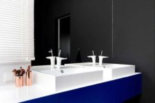 this modern master bathroom features black and white striped flooring, a black wall, and a bright blue vanity