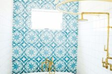 white tiles paired with blue mosaic ones and with gold touches for a bright and welcoming space