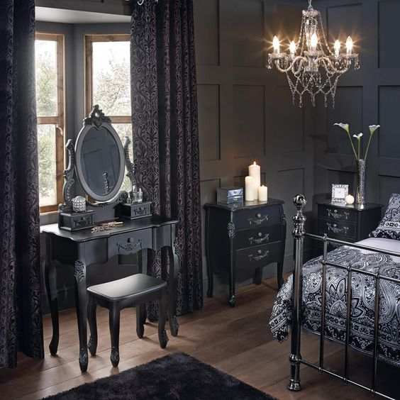 a Gothic space with graphite grey paneling, refined furniture, a forged bed, a crystal chandelier and dark linens