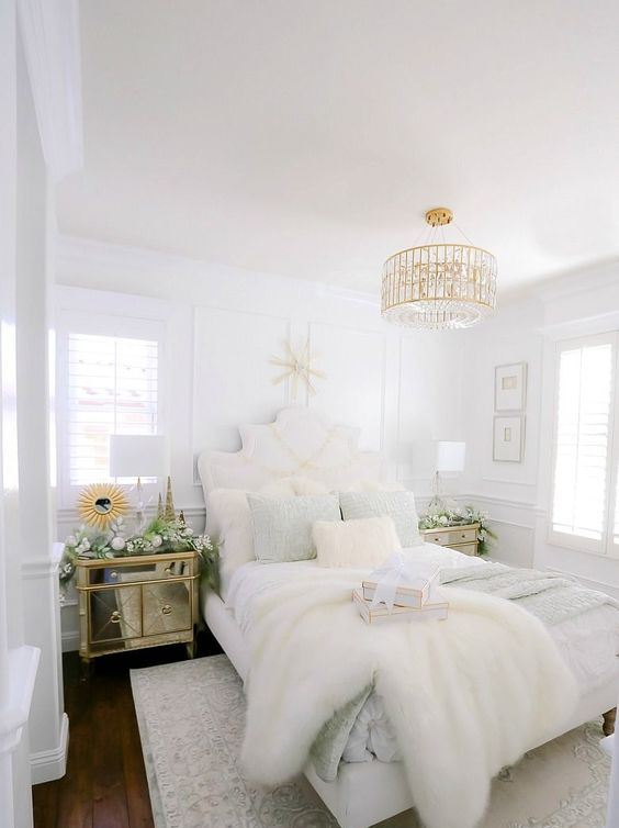 a beautiful glam bedroom in neutrals, with a gold and crystal chandelier, refined furniture, a mirror nightstand and rugs
