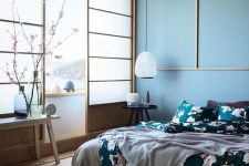 a beautiful zen-like bedroom with traditional Japanese sliding doors, a low bed and wooden furniture, blue walls and a ceiling, floral bedding