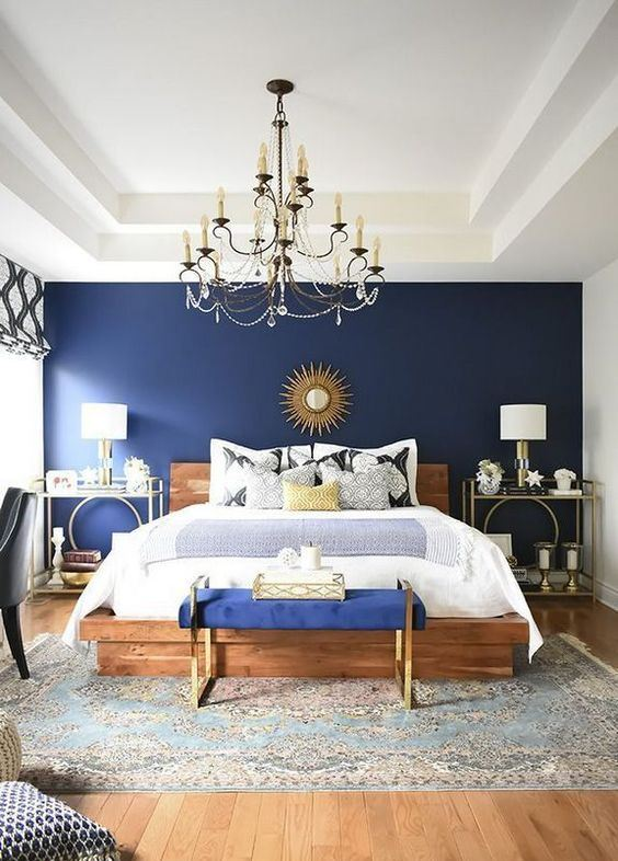 a boho glam bedroom with a navy statement wall and bench, a crystal chandelier, creative nightstands and candles