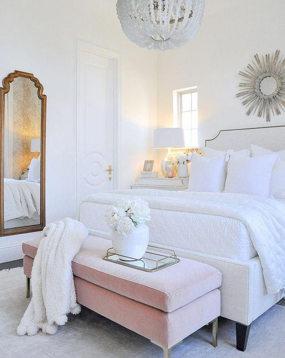 a chic glam bedroom in white with an upholstered bed and bench, a vintage mirror, a crystal chandelier and a sunburst mirror