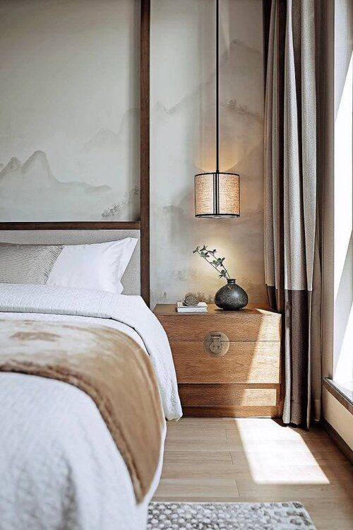 a chic neutral bedroom with mountain panels on the walls, a wooden nightstand and an upholstered bed, pendant lamps and color block curtains