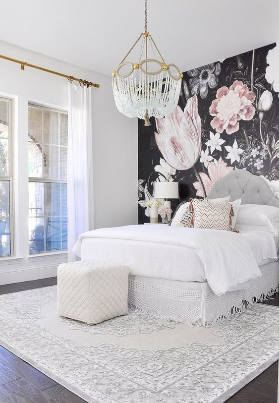 a contemporary glam bedroom with a statement floral wall, a crystal chandelier, a white ottoman and a printed rug