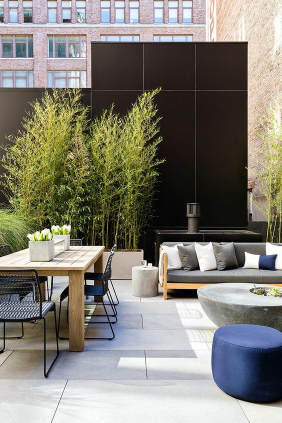 a cool modern terrace with simple furniture, a concrete table, a wooden dining table and metal chairs plus potted greenery