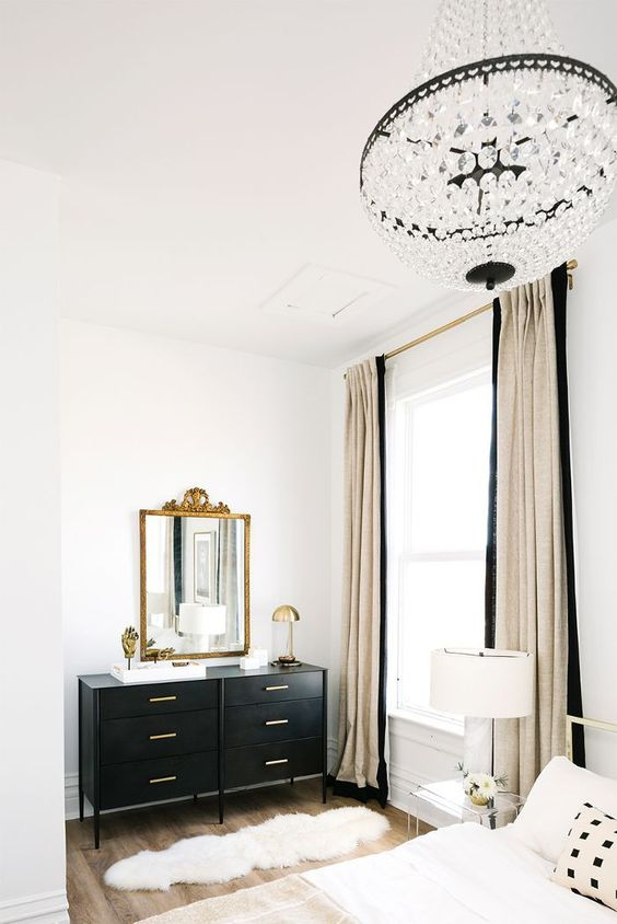 a glam Parisian bedroom in neutrals and black, with a crystal chandelier, a black sideboard, a gold mirror and lamps