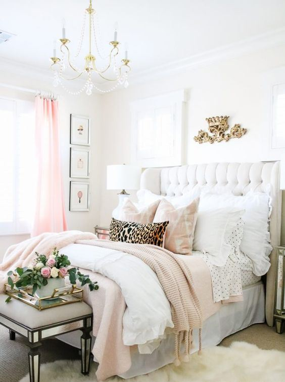 a glam pink, gold and neutral bedroom with a mirror bench, a white leather bed, a crystal chandelier and pink touches