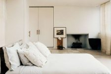 a low-key zen bedroom with a bed placed on a wooden platform, exquisite furniture and a built-in fireplace, a glazed ceiling
