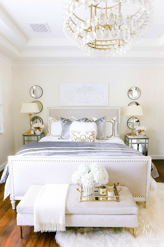 a luxurious glam bedroom in neutrals with a crystal chandelier, mirror nightstands, an upholstered bed, mirrors and a tray