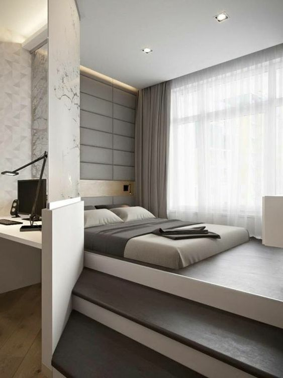 a minimalist and all zen bedroom with a bed placed on a platform, a white nightstand, neutral bedding and an upholstered wall