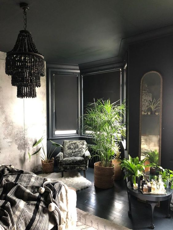 a modern Gothic bedroom with black paneled walls, an abstract print wardrobe, dark furniture, potted plants and a black beaded chandelier