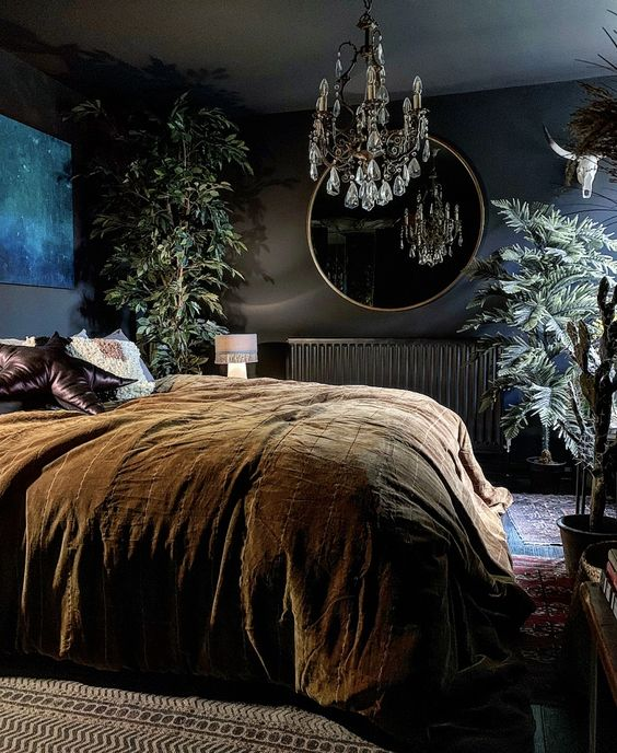 a modern Gothic bedroom with black walls, a bright artwork, a round mirror, a crystal chandelier and potted plants