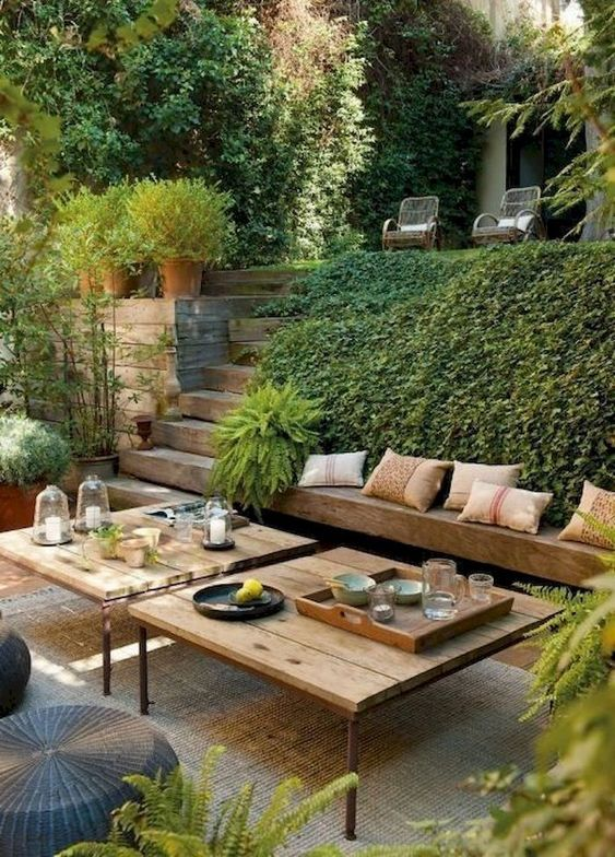 a modern Mediterranean terrace with a built-in bench, modern furniture, wicker ottomans and lots of greenery