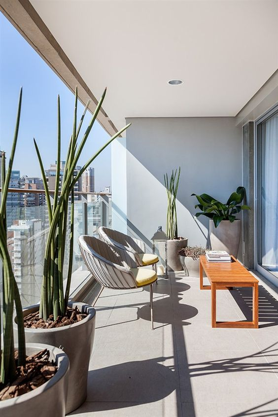 a modern balcony terrace with potted plants, metal chairs, a wooden table and a candle lantern