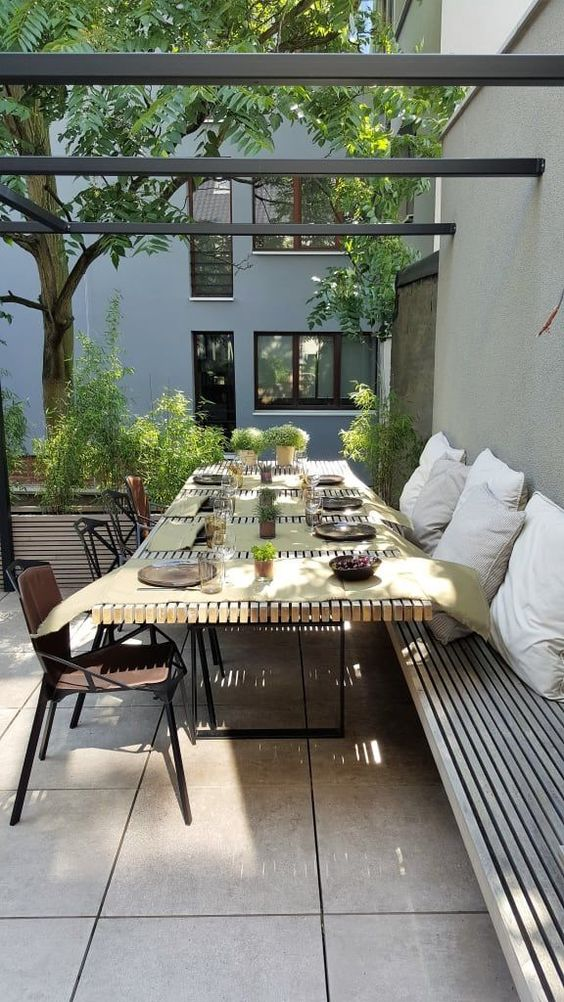 a modern outdoor dining space with built-in benches, a slab table, metal chairs and lots of potted greenery