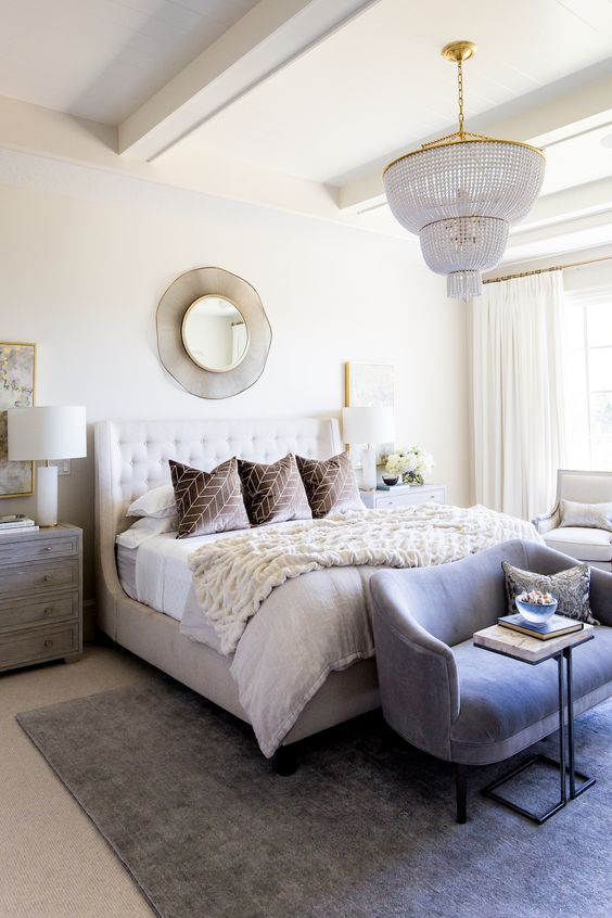a modern glam bedroom in neutrals, with an upholstered bed, a crystal chandelier, a grey bench, a mirror and rugs