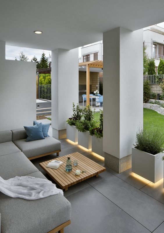 a modern patio with lit up pots with greenery, an L-shaped sofa and a wooden slab table in the center