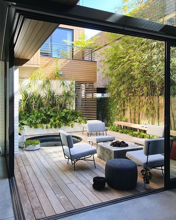 a modern patio with lots of greenery, a hot tub, a concrete firepit, grey chairs and a wicker ottoman