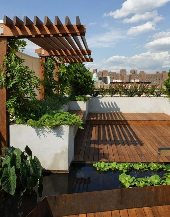 a modern rooftop terrace with a deck, built-in benches, lots of potted greenery and a pond of a geometric shape in a metal cover