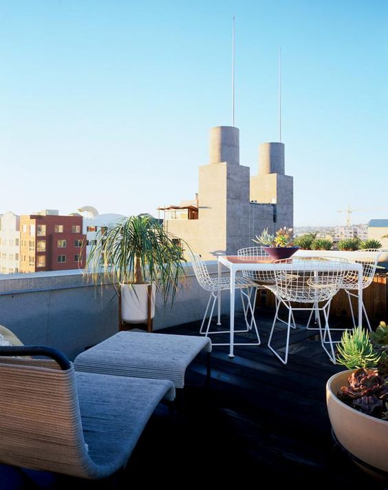 a modern rooftop terrace with a wicker lounger and a footrest, metal furniture, potted plants and a cool view