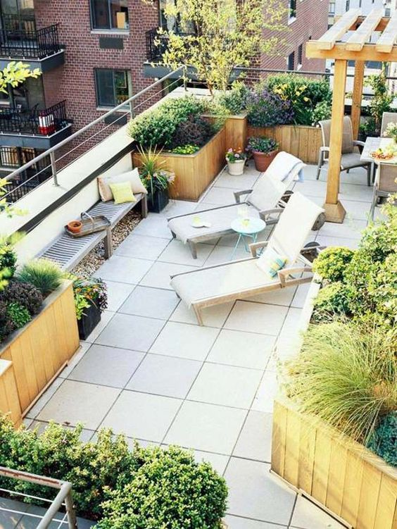a modern rooftop terrace with loungers, a bench with bright pillows, lots of potted greenery and blooms