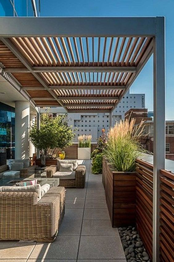 a modern rooftop terrace with wicker furniture, a firepit coffee table and some potted plants here and there