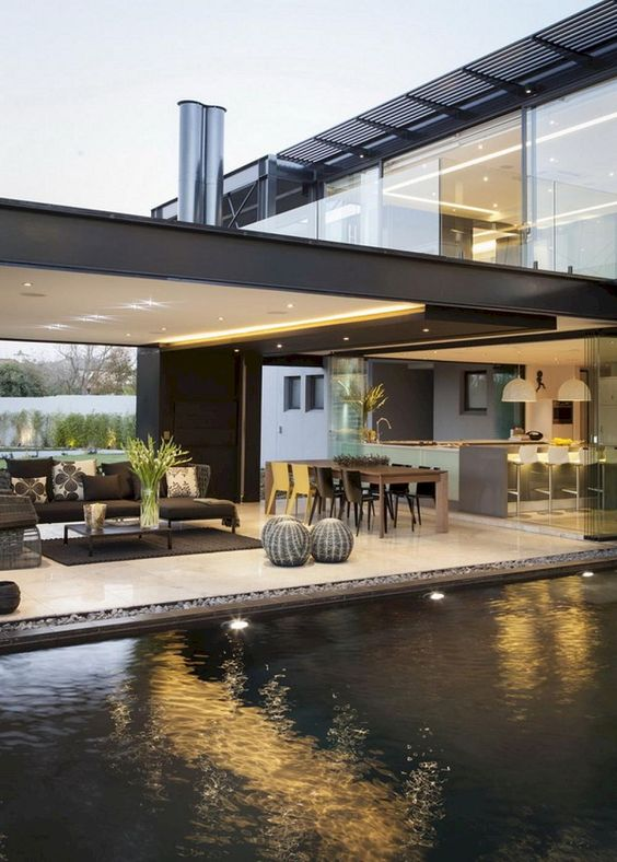 a modern terrace by the pool, a living room space and a dining zone plus built-in lights