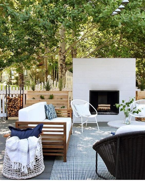a modern terrace with a built-in fireplace, a striped rug, wicker chairs, a wooden sofa and a basket