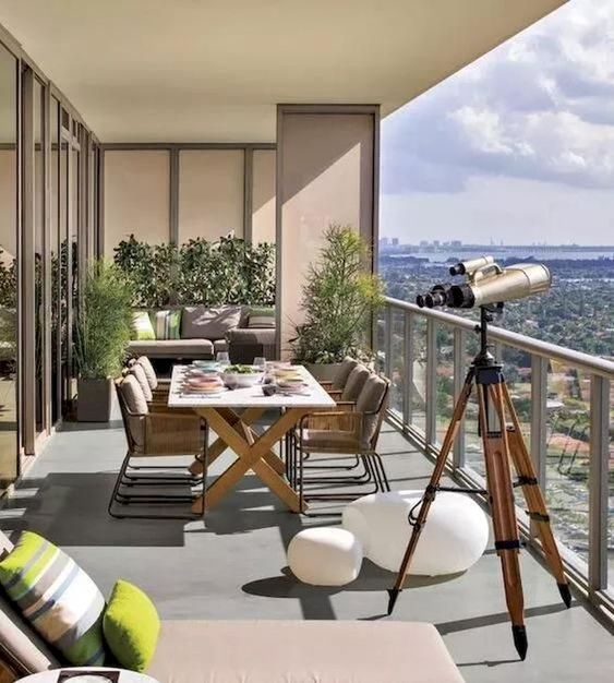 a modern terrace with a trestle table, metal chairs, potted greenery and a lounger plus cool views
