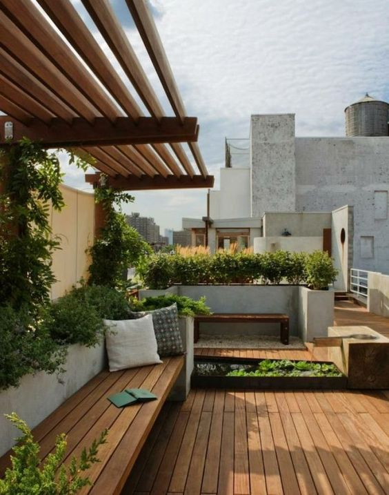 a modern terrace with a wooden deck, built-in furniture, a concrete lanter with greenery and other planters