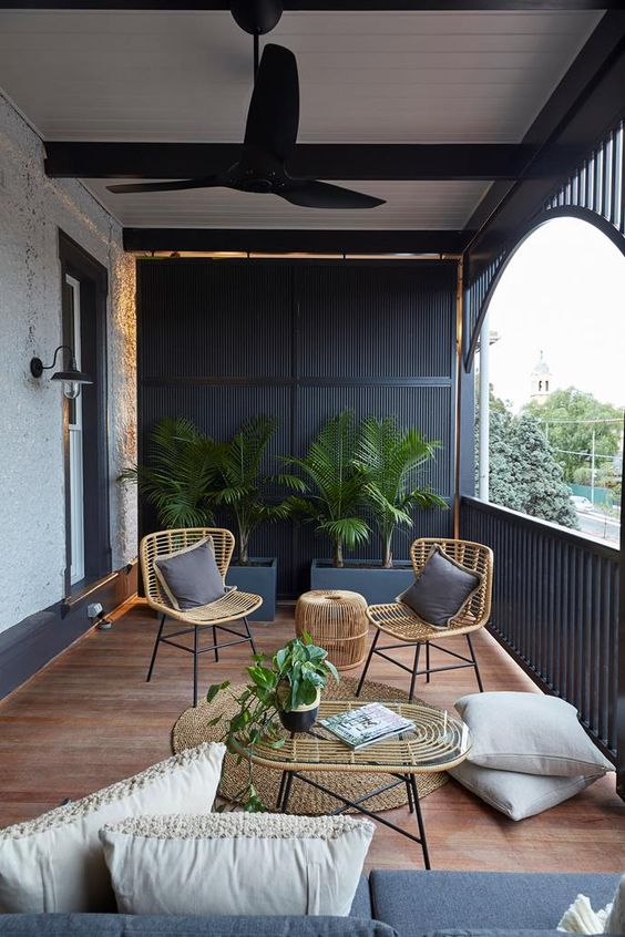 a modern terrace with black wooden slabs, wicker furniture, grey and neutral upholstery and potted greenery