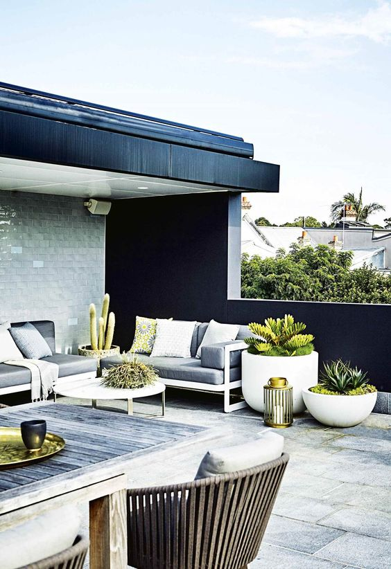 a modern terrace with grey furniture, potted greenery, candle lanterns, a weathered wood table and wicker chairs