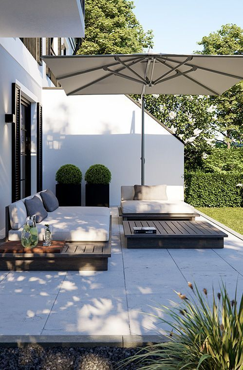 a modern terrace with potted greenery, crate furniture and a large umbrella over the space