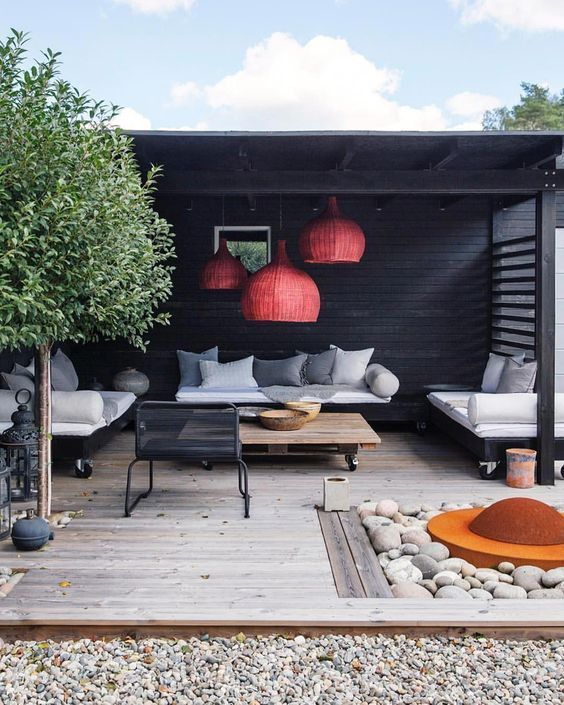 a modern terrace with red wicker lamps, modern furniture on casters, a fire pit with pebbles around and a tree