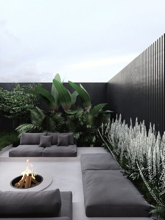 a modern terrace with simple low furniture, a firepit and lots of bold statement plants around the space