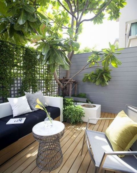 a modern terrace wityh wood and metal furniture, a wire table, greenery and a tree with a fountain