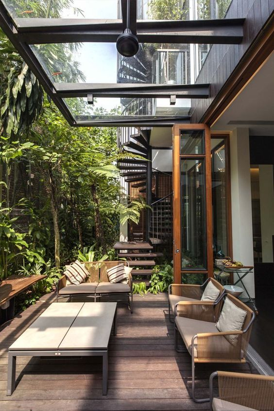 a modern tropical terrace with metal and woven furniture, a wooden table and lots of greenery growing around