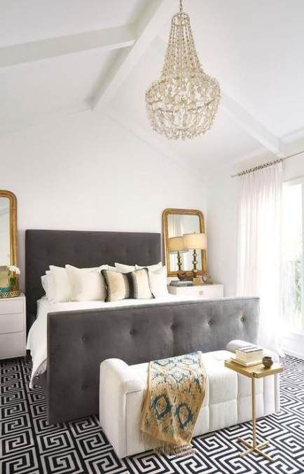 a monochromatic bedroom with gold touches, a crystal chandelier, gold frame mirrors and a table, a grey upholstered bed