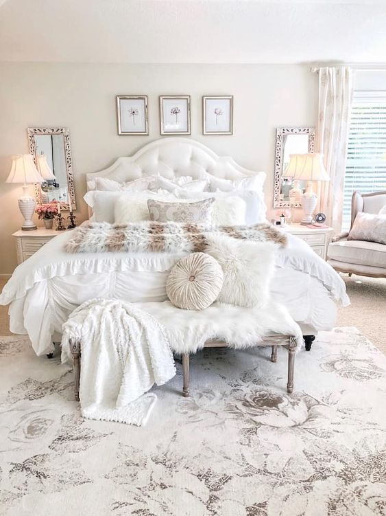 a neutral and pastel glam bedroom with a gallery wall, mirrors, lamps, a shabby chic bench and cool textiles