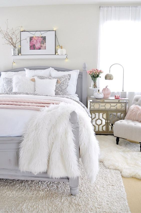 a neutral glam bedroom with a grey bed, mirror nightstands, faux fur rugs, blooms and lights over the bed