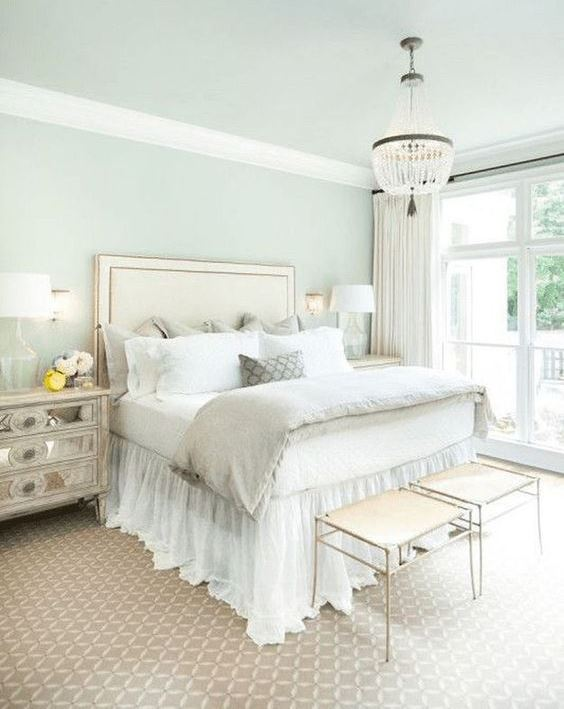 a neutral glam bedroom with an upholstered bed, a crystal chandelier, mirror nightstands and elegant stools