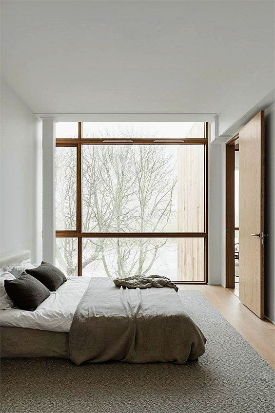 a neutral zen bedroom with a bed right on the floor and a glazed wall to enjoy the views plus neutral linens and bedding