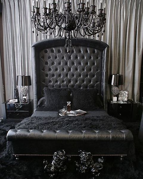 a refined Gothic bedroom with a black leather bed, glossy nightstands, a refined black chandelier and elegant detailing
