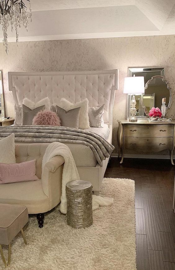 a refined glam bedroom in neutrals, silver furniture, a white upholstered bed, touches of pink and a crystal chandelier