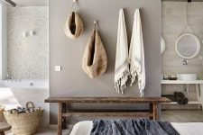 a relaxed zen bedroom united with a bathroom, with stone and concrete walls, a wooden bench, neutral bedding and baskets for storage