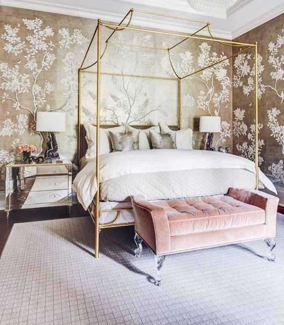 a romantic glam bedroom with botanical print walls, a glam gold bed, a pink bench, mirror nightstands