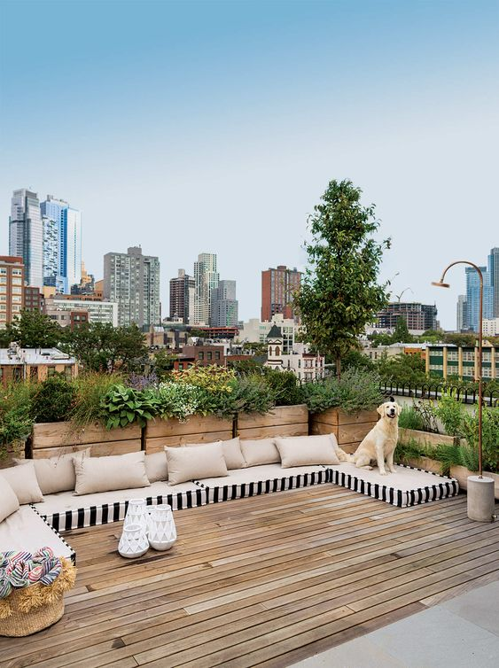 a simple and modern rooftop terrace with a wooden deck, mattresses instead of sofas and potted greenery