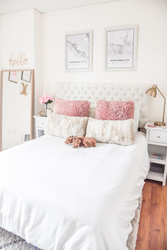 a simple glam bedroom with touches of brass, a white bed, some art and calligraphy for a teen