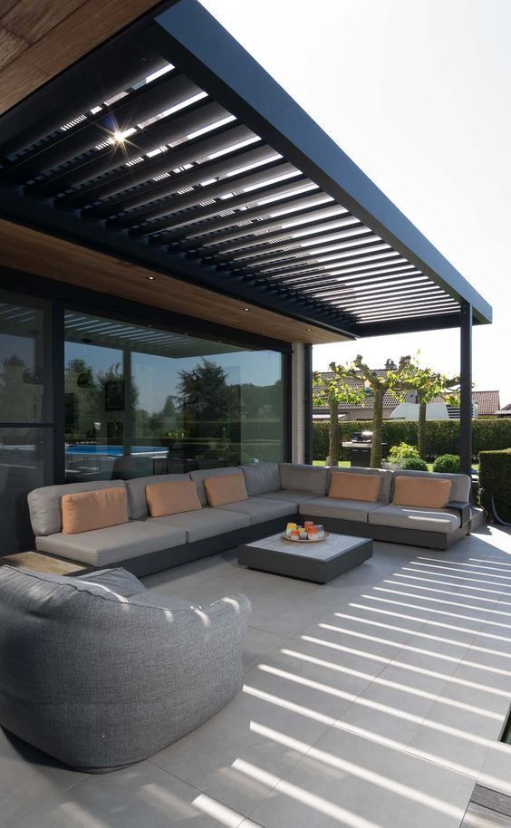 a simple modern terrace under a beamed roof, an L-shaped sofa, a beanbag chair and a coffee table
